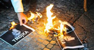 A man burns trokia signs during an anti-austerity and anti-governmental protest in Ljubljana, Slovenia, on Tuesday. Photograph: Srdjan Zivulovic/Reuters