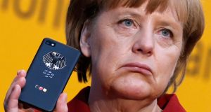 Angela Merkel holds a BlackBerry Z10 smartphone featuring high security  software, used for governmental communication, at a computer fair in Hanover in in March this year. Photograph: Reuters