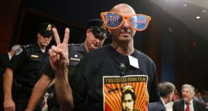 A protester against US spying is escorted by Capitol Police from a hearing yesterday in which US director of national intelligence James Clapper testified on potential changes to the Foreign Intelligence Surveillance Act. Photograph: Jason Reed/Reuters