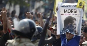 An Al-Azhar University student holds up a poster of ousted Egyptian president Mohamed Morsi, as members of the Muslim Brotherhood and supporters Mr Morsi, shout slogans against the military and interior ministry, near Rabaa al-Adawiya square in Cairo. Photograph: Amr Abdallah Dalsh/Reuters.