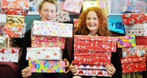 Christmas box: Jack Scollard and Amy Logan of  High School, Rathgar, with some of the boxes they and their schoolmates wrapped and filled for Team Hope. Photograph: Krista Burns