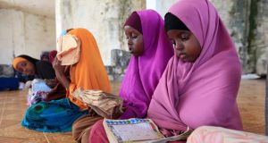 Life in Mogadishu: girls read during a Koranic studies lesson.  Photograph: Feisal Omar/Reuters