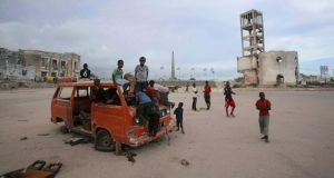 Life in Mogadishu: children play on an abandoned truck in front of the destroyed former parliament building. Photograph: Feisal Omar/Reuters