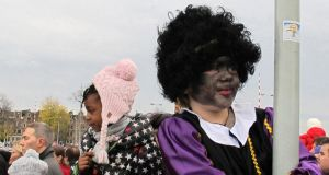 "A child  dressed as ""Zwarte Piet"" or ""Black Pete""watches a parade after St Nicholas, or Sinterklaas, arrived by boat in Amsterdam last year. Photograph: AP"