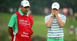 Rory McIlroy looks dejected on the 16th green as his caddie JP Fitzgerald looks on during the third round of the WGC - HSBC Champions at the Sheshan International Golf Club. Photograph: Andrew Redington/Getty Images