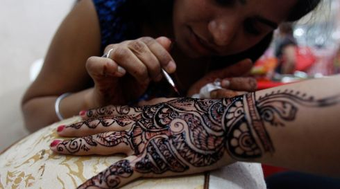A woman applies henna on the hand of a customer at a Deepavali Bazaar at Little India in Singapore. Photograph: Edgar Su/Reuters