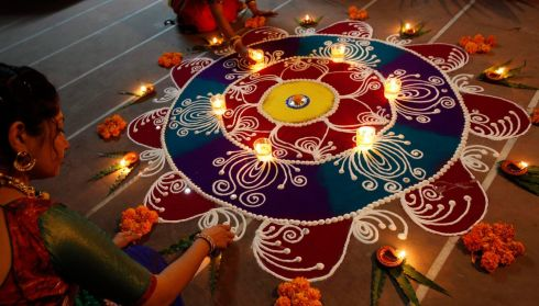 Hindu women arrange oil lamps and flowers around a 'Rangoli', a traditional pattern made from coloured powders, during the celebrations ahead of the Hindu festival of Diwali in the western Indian city of Ahmedabad. Photograph: Amit Dave/Reuters