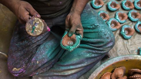 A worker spray-paints Diwali diyas, or earthenware lamps, at a pottery near Sarojini Market in New Delhi, India. Photograph: Prashanth Vishwanathan/Bloomberg