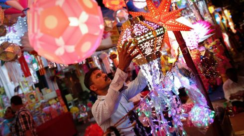 A vendor hangs a lantern for sale at a Diwali market in Mumbai, India. Photograph: Danish Siddiqui/Reuters