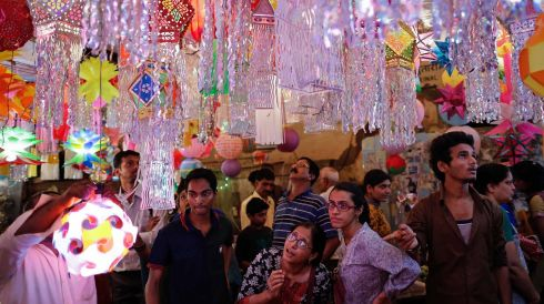 Customers stand under lanterns for sale at a Diwali market in Mumbai. Photograph: Danish Siddiqui/Reuters