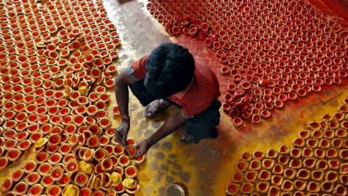 A worker paints earthen lamps ahead of the Hindu festival of Diwali in Kolkata, India. Photograph: Rupak De Chowdhuri/Reuters