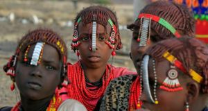 Girls from the Daasanach tribe sit outside their hut at the venue of a welcoming ceremony for tourists ahead of the hybrid solar eclipse expected to take place today, at the remote Sibiloi National Park on the shores of Lake Turkana in Kenya.  Photograph: Reuters