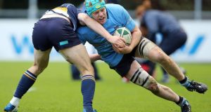 UCD's Conor Gilsenan is tackled by Darren Sweetnam of Dolphin. Photograph: Cathal Noonan/Inpho