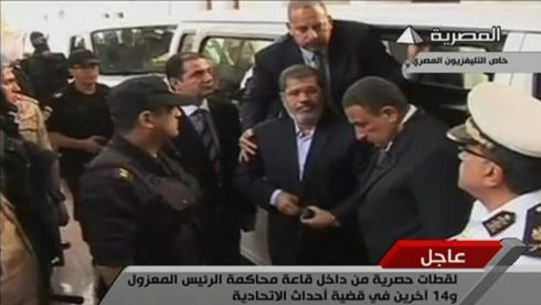 Ousted former Egyptian president Mohamed Morsi steps out of a van as he arrives at a courthouse on the first day of his trial in Cairo today. Following days of uncertainty about whether Morsi would even be allowed to attend, he entered the courtroom shortly after 10am, his 14 colleagues greeting him with a polite round of applause Photograph: Egypt State TV/Reuters TV