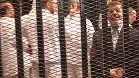Ousted former Egyptian president Mohamed Morsi stands in a cage in a courthouse in Cairo, today. His co-defendants, dressed in white, make the four-fingered Raba'a sign in solidarity with the Muslim Brotherhood behind him. Photograph: Egypt Interior Ministry/Handout via Reuters