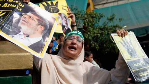 "A supporter of ousted Egyptian president Mohamed Morsi cries while holding his poster and a ""Rabaa"" poster (right) outside the Egyptian High Court in Cairo. The ""Rabaa"" or ""four"" gesture is in reference to the police clearing of Rabaa al-Adawiya protest camp on August 14.  Photograph: Mohamed Abd El Ghany/Reuters"