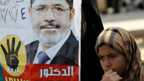 A supporter of the Muslim Brotherhood and ousted Egyptian president Mohamed Morsi stands next to a poster of Mr Morsi during a protest outside the police academy. Photograph: Amr Abdallah Dalsh/Reuters