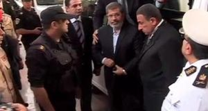 This image made from video shows ousted Egyptian president Mohamed Morsi, centre, arriving for a trial hearing in Cairo, yesterday. Emerging from four months in secret detention, the deposed Islamist president defiantly rejected the court's authority to try him. Photograph: AP photo/Egyptian interior ministry