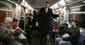 New York City Democratic mayoral nominee Bill de Blasio greets commuters while riding the R train from the Bay Bridge neighborhood of Brooklyn on his way to a campaign stop, in New York.