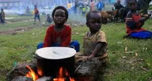 Children, displaced by fighting between the Congolese army and M23 rebels in Bunagana in the eastern Democratic Republic of Congo, sit around a pot in a field with other displaced families in the Ugandan town of Bunagana, 491 km (305 miles) west of the capital Kampala, this week. Photograph: James Akena/Reuters