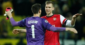 Arsenal's goalkeeper Wojciech Szczesny and team-mate Per Mertesacker (right) celebrate after defeating Borussia Dortmund in their Champions League Group F  match on Wednesday. Photograph: Ina Fassbender/Reuters