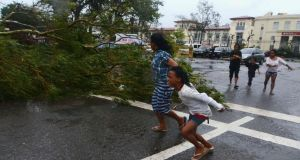 Residents rush to safety past a fallen tree during strong winds brought by Typhoon Haiyan that hit Cebu city, central Philippines today. Photograph: Zander Casas/Reuters.