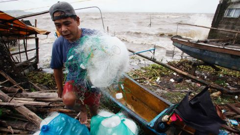 A fisherman carries his net after making it safely back to shore in the fishing village after a strong winds from Typhoon Haiyan battered Bayog town in Los Banos, Laguna city, south of Manila. Photograph: Charlie Saceda/Reuters