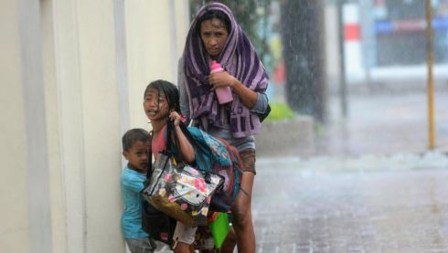 A mother takes refuge with her children as Typhoon Haiyan hits Cebu city, central Philippines. Typhoon Haiyan, the strongest typhoon the world has seen this year and possibly the most powerful ever to hit land battered the central Philippines today, forcing millions of people to flee to safer ground, cutting power lines and blowing apart houses. Photograph: Zander Casas/Reuters