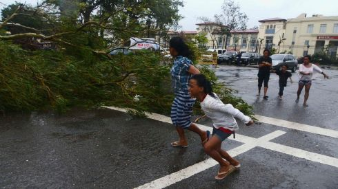 Residents rush to safety past a fallen tree during strong winds brought by Typhoon Haiyan in Cebu city. Haiyan, a category-5 super typhoon, bore down on the northern tip of Cebu Province, a popular tourist destination with the country's second-largest city, after lashing the islands of Leyte and Samar with 275 kph (170 mph) wind gusts and 5-6 meter (15-19 ft) waves.   Photograph: Zander Casas/Reuters