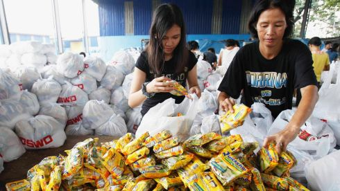 Volunteers pack a relief goods in a warehouse before shipping out to devastated provinces hit by Typhoon Haiyan in Manila. Photograph: Romeo Ranoco/Reuters