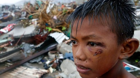 A boy who was wounded by flying debris due to Super Typhoon Haiyan stays at the ruins of his family's house in Tacloban city. Photograph: Erik De Castro/Reuters
