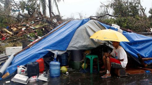 A typhoon victim sits under an umbrella outside a makeshift tent after Super Typhoon Haiyan battered Tacloban city in central Philippines. Photograph: Erik De Castro/Reuters