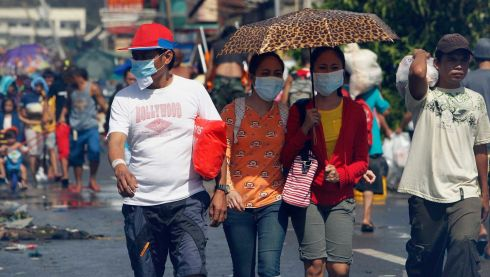 Survivors wearing face masks walk downtown after super Typhoon Haiyan battered Tacloban city, central Philippines. Photograph: Romeo Ranoco/Reuters