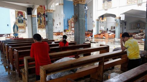 Residents pray inside a damaged catholic church after super Typhoon Haiyan battered Tacloban city, central Philippines. Photograph: Romeo Ranoco/Reuters