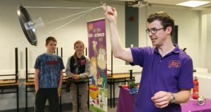 Terence Finnegan ,  spins a glass of water on a tray ,  to demonstrate centrifugal forces for Roisin Clarke and Mark Coen , who are keeping a safe distance, at the annual Science and Technology Fair as part of Science Week Ireland,  in the Institute of Technology, Sligo,  yesterday yesterday. Photograph: James Connolly