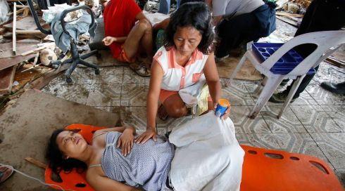A woman comforts a pregnant relative before she delivered her baby at a makeshift birthing clinic in typhoon battered Tacloban city in central Philippines today. Photograph: Reuters
