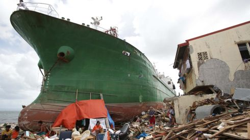 Survivors stay beside a ship that was washed ashore hitting makeshift houses near an oil depot in Tacloban city, Leyte province central Philippines today.