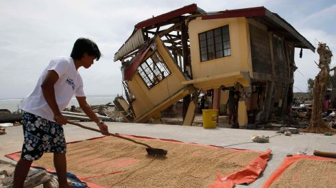 A man dries rice bran in front of his house damaged by  typhoon Haiyan in Hernani, Samar, in central Philippines today. Photograph: Reuters