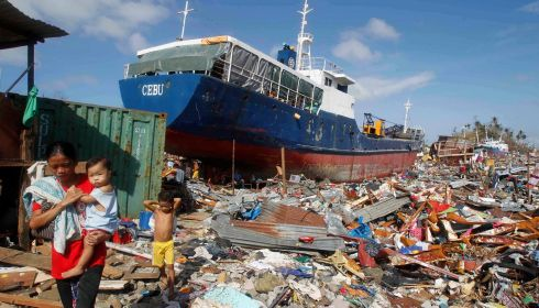 People walk past a cargo ship washed ashore in the wake of typhoon Haiyan. Photograph: Reuters