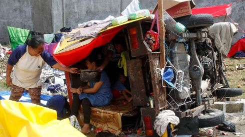 Homeless residents sit inside a damaged vehicle used as a makeshift shelter in the wake of the typhoon. Photograph: Reuters