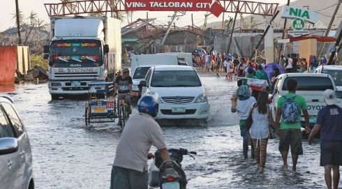 People wade through flood waters yesterday in Tacloban City. Photograph: Getty Images.