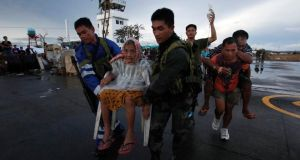 Filipino soldiers bring Tacloban residents to a military plane leaving Tacloban airport in central Philippines. Photograph: Reuters/Bobby Yip