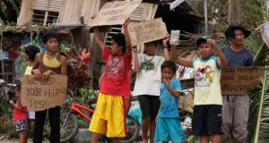 Children hold signs asking for help and food along the highway after Typhoon Haiyan hit Tabogon town in Cebu province. Photograph: Reuters/Charlie Saceda