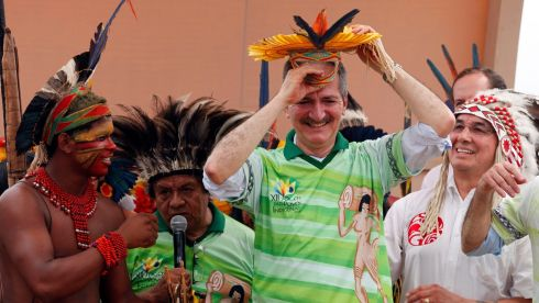 Brazil's sports minister Aldo Rebelo tries on a tribal accessory given to him by a member of the Pataxo during the Games.  Photograph: Paulo Whitaker/Reuters