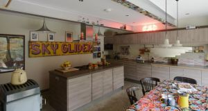 The kitchen is a kitsch mix of vintage signs, Ikea units and fridge magnets used decoratively to make a feature of the girder. An oilcloth cheers up the table.