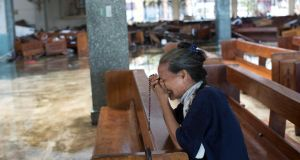 A women sobs while praying in a  flooded church in Tacloban, Philippines, on Thursday,  six days after the city was largely destroyed by typhoon Haiyan. Photograph: Tyler Hicks/New York Times.