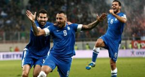 Greece's Kostas Mitroglou (centre), Dimitris Siovas (left) and Alexandros Tziolis celebrate a goal against Romania  at Karaiskaki stadium in Piraeus, near Athens. Photograph: Reuters