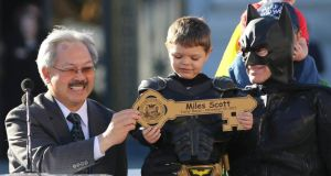 'Bat Kid' Miles Scott receives a key to the city  from  Mayor Ed Lee  during a ceremony at San Francisco City Hall.  Photograph: Robert Galbraith/Reuters