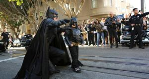 Holy Hotcakes! They went thataway! Batman and Batkid on the trail of the bad guys in  San Francisco. Photograph: Robert Galbraith/Reuters
