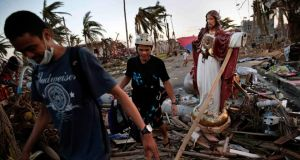 Residents walk past a statue of Jesus Christ in the rubble of a neighbourhood  in Tacloban that was devastated by Typhoon Haiyan.  Photograph: Kevin Frayer/Getty Images